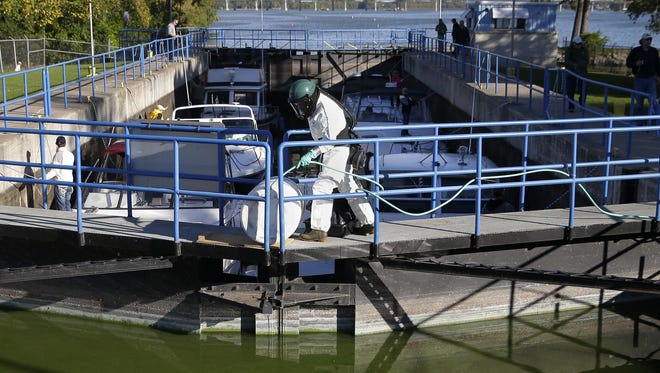 Mark Baldock of the Wisconsin Department of Natural Resources prepares a container with Rotenone, a naturally occurring pesticide, before it is released in the Menasha lock in 2015. The treatment allowed the lock to reopen for one day so boaters could take their crafts to winter storage sites.