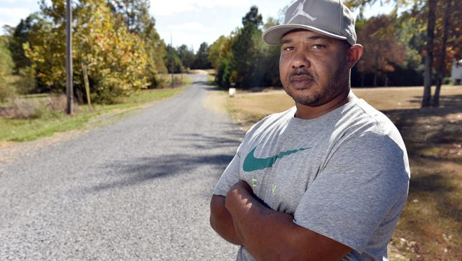 Michael Buckley stands on the newly paved street outside his home on Hayes Place outside Richland.