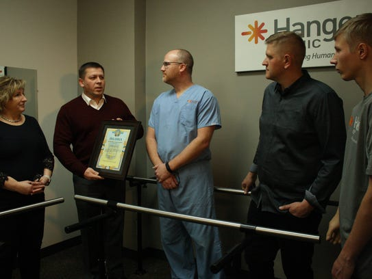 Ryan Stark (center) is presented with a certificate