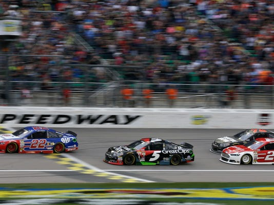 NASCAR driver Joey Logano (22) takes the lead over Kasey Kahne (5) and the rest of the pack during the first lap of a Sprint Cup Series auto race at Kansas Speedway in Kansas City, Kan., Saturday, May 9, 2015. (AP Photo/Orlin Wagner)