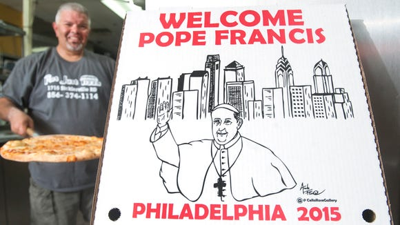 John Maniscalco, owner of Not Just Pizza in Sicklerville, prepares to place a pizza into a box that welcomes Pope Francis.  The boxes were designed by Amanda Farese, Director of Marketing for Savona Stavola and self taught artist.