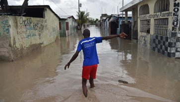 A man walks down a flooded street in the neighhorhood of Cite Soleil in Port-au-Prince, Haiti, on Oct. 4, 2016.