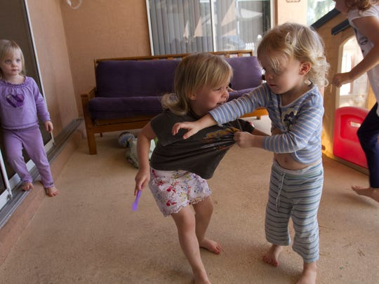 Ashley and Tabitha Anderson tussle over a toy at their Cape Coral home Friday, March 14.