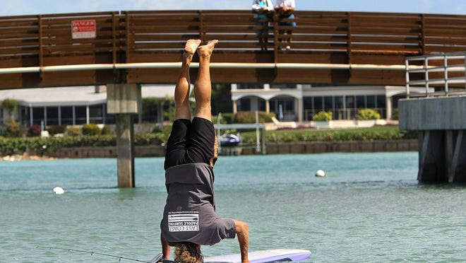 In this file photo, John Denney, of Jupiter, does a handstand on his 12-foot paddleboard at DuBois Park in Jupiter. The Palm Beach Paddlefest will be held on Saturday at Harbourside Place.
