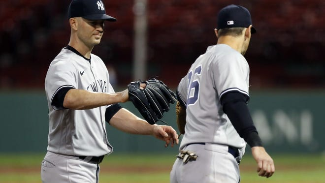 New York Yankees' J.A. Happ, left, taps gloves with DJ LeMahieu (26) as he walks to the dugout after pitching during the eighth inning of a baseball game against the Boston Red Sox, Saturday, Sept. 19, 2020, in Boston.