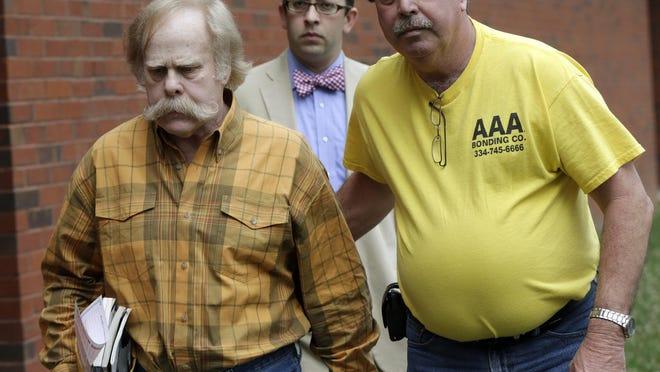 Harvey Updyke, left, leaves the Lee County Justice Center in Opelika on June 10, 2013, with his bail bondsman and his attorney. Updyke, the University of Alabama fan convicted of poisoning Auburn University's Toomer's Corner oak trees, died Thursday, according to his son. He was 71.