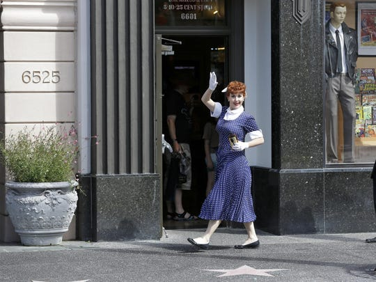A Lucille Ball character waves to guests as she walks along Hollywood Boulevard at Universal Studios in Orlando, Fla.