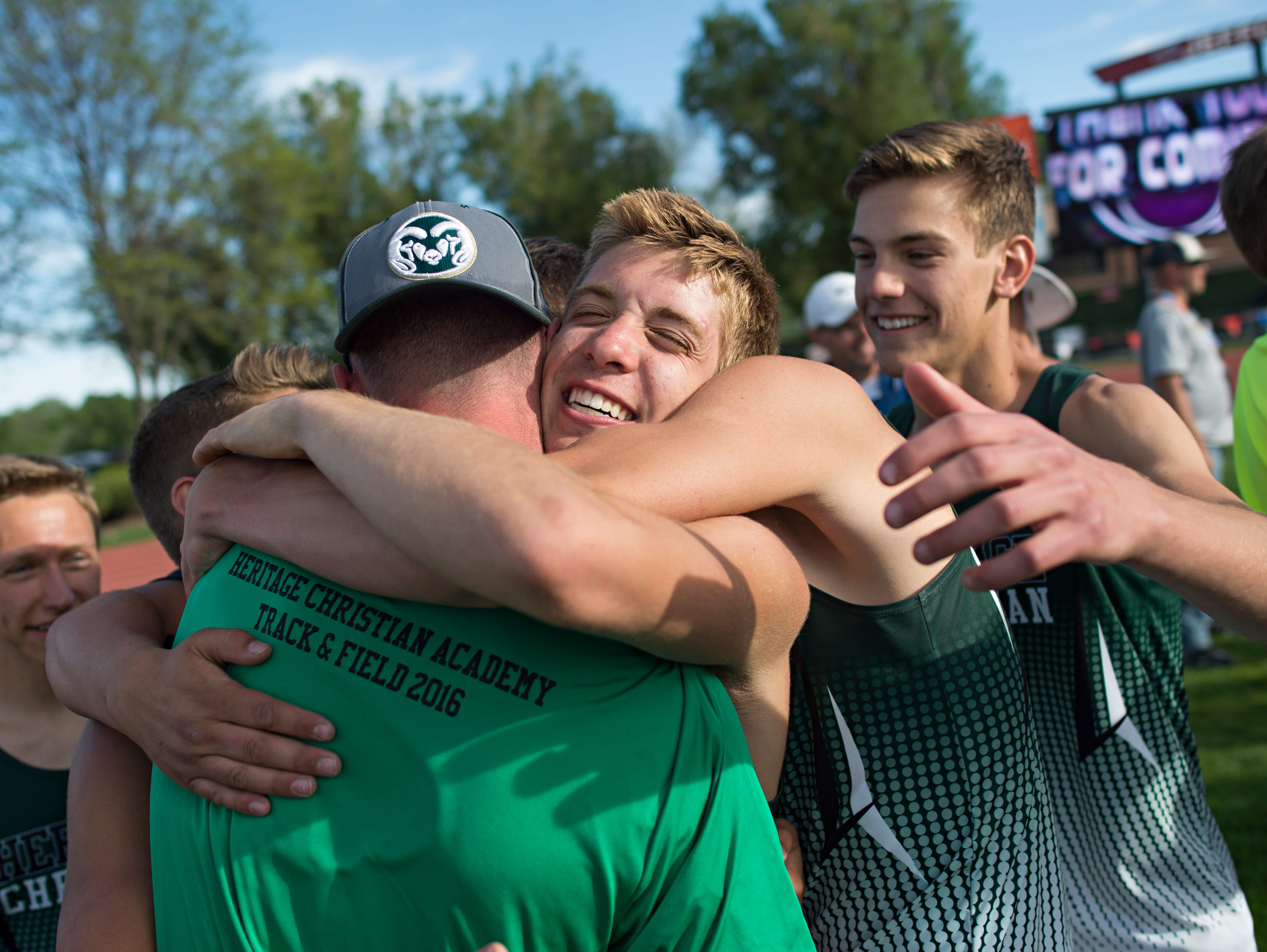 Luke Gilliland of Heritage Christian Academy hugs assistant coach Todd Ellerbe Saturday after the Eagles received their trophy for winning the Class 1A boys team title at the Colorado state track and field championships at Jeffco Stadium. Heritae Christian also won the 1A girls team title.