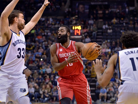 Houston Rockets guard James Harden, center, drives