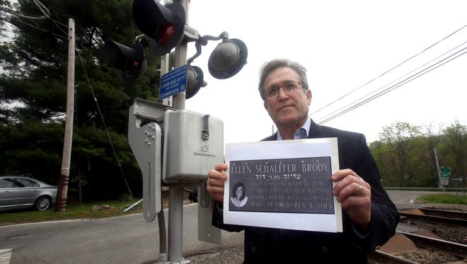 Alan Brody, husband of Ellen Brody, holds a photo of the memorial stone at his wife's grave while visiting the Metro-North railroad crossing at Commerce Street in Valhalla May 13, 2016. Ellen Brody and five others were killed when the vehicle she was driving was struck by a Metro-North train at the crossing in February of 2015. Assemblyman Thomas Abinanti and State Sen. David Carlucci are trying to get legislation passed that they hope will improve railroad crossing safety.