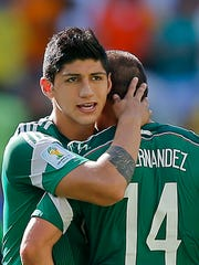 FILE - In a June 29, 2014 file photo, Mexico's Alan Pulido consoles teammate Javier Hernandez (14) after the Netherlands defeated Mexico 2-1 during the World Cup round of 16 soccer match between the Netherlands and Mexico at the Arena Castelao in Fortaleza, Brazil.