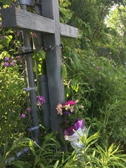 Cross, flowers mark scene north of Kalamazoo where 5 cyclists were killed when a truck hit them Tuesday, June 7, 2016.