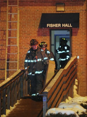 Indianapolis firefighters exit a side door of Fisher Hall on the Marian University campus after a small fire Feb. 17, 2014. The  building in the 3200 block of Cold Springs Road is used by the visual arts program..