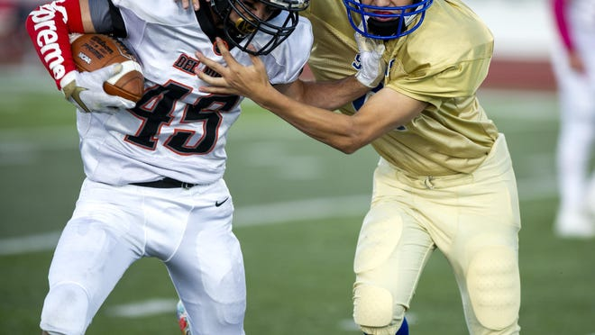 Dolores Huerta Prep's Mateo Mata, right, tries to bring down Del Norte running back Marcos Romero on Sept. 20, 2019, at the Neta and Eddie DeRose ThunderBowl.