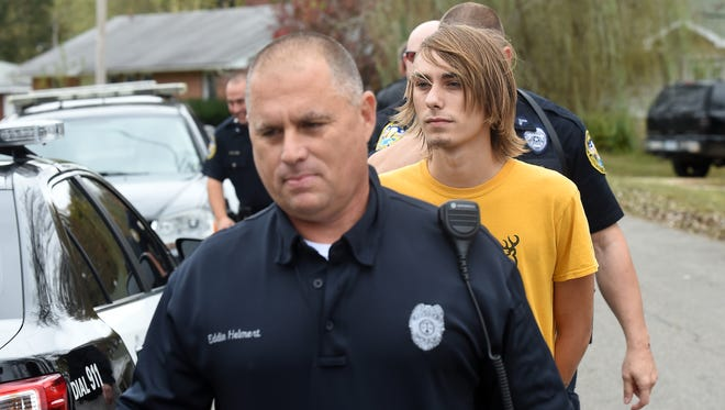Mountain Home Police officer Eddie Helmert leads Austin Mikel Short, 18, of Midway to a patrol car on Monday. Short led police on a short chase Monday near Mountain Home High School. He was arrested on breaking and entering charges.