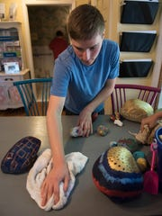 Andrew Tegler wipes the kitchen table at the center, which helps people with autism.