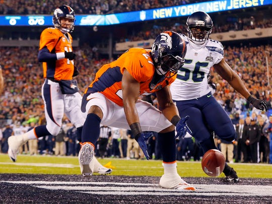 FILE - In this Feb. 2, 2014, file photo, Denver Broncos' Knowshon Moreno reaches for a loose ball after the snap passed teammate Peyton Manning, left, during the first half of the NFL Super Bowl XLVIII football game, in East Rutherford, N.J. Seattle Seahawks' Cliff Avril approaches at right. Moreno dove on it for a safety. Seattle defeated Denver 43-8. (AP Photo/Paul Sancya)