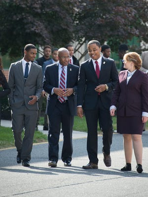 Harry Williams walks on campus with Delaware State University students.