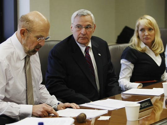 Howard Birdsall (left) when he was chairman of the Brookdale Community College board of trustees, announces the school's one-time president, Peter Burnham, was put on leave without pay in 2011. Center is Josh Elkes, vice-chairman, followed by Joan Raymond, trustee.