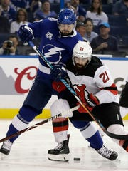 New Jersey Devils right wing Kyle Palmieri (21) hits Tampa Bay Lightning left wing Alex Killorn during the second period of Game 5 of an NHL first-round hockey playoff series Saturday, April 21, 2018, in Tampa, Fla.