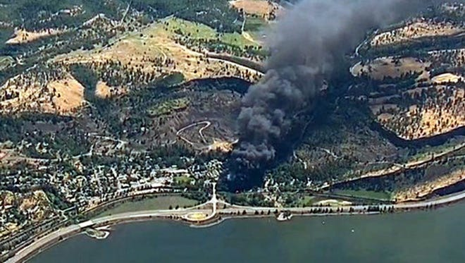 In this June 3, 2016, file frame from video provided by KGW-TV, smoke billows from a Union Pacific train that derailed near Mosier, Ore., in the scenic Columbia River Gorge. safety officials say they've seen slow progress in efforts to upgrade or replace tens of thousands of rupture-prone rail cars used to transport oil and ethanol, despite a string of fiery derailments.