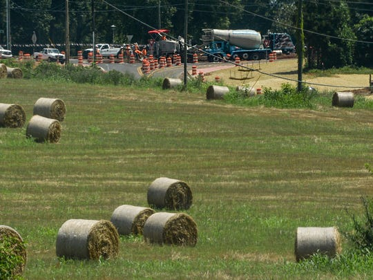 Looking past a field of hay bales on Concord Road, where construction of a roundabout is finishing up this summer in Anderson. The project, the first roundabout in Anderson, is a state roads funded project in progress during the summer of 2018.