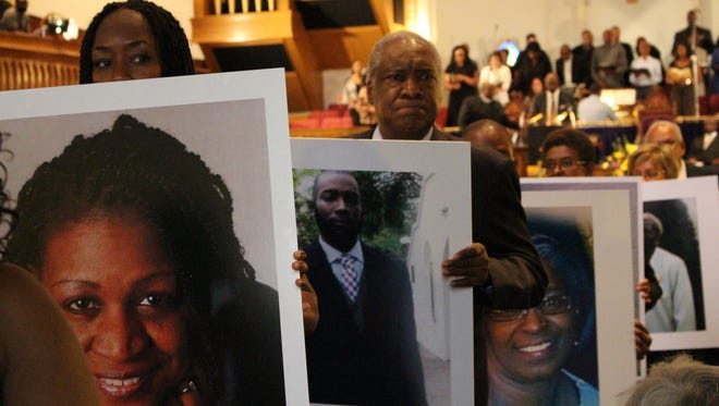 Members of the Metropolitan AME Church in Washington, D.C., carry images of the victims of the Charleston shooting during a vigil on June 19, 2015.