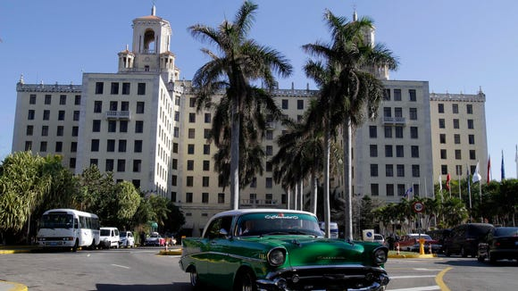 An antique Chevrolet car pulls out of Hotel Nacional