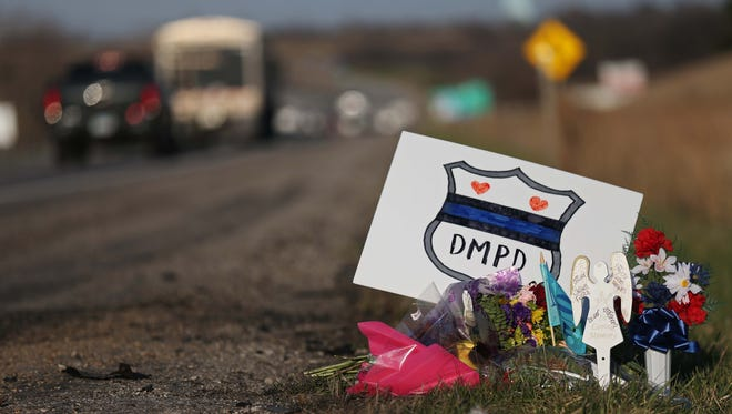 A roadside memorial on the side of Interstate 80 on Monday, March 28, 2016, honors Susan Farrell and Carlos Puente-Morales, Des Moines police officers killed in a car crash at this spot on March 26.