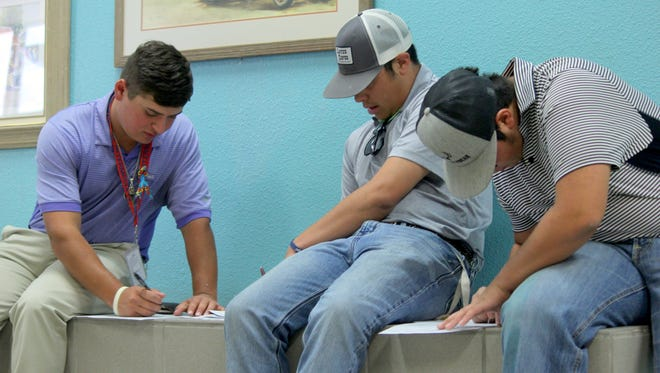 From left, Isaac Sifuentes, Chuck Parker and Jordan Perales fill out job applications during Wednesday's Job Fair at the Special Events Center.
