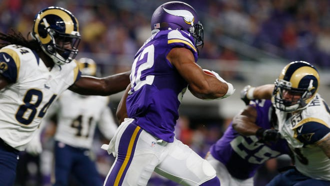Minnesota Vikings running back Jhurrell Pressley, center, runs from Los Angeles Rams' Temarrick Hemingway, left, while returning a kickoff for a touchdown during the second half of an NFL preseason football game Thursday, Sept. 1, 2016, in Minneapolis.