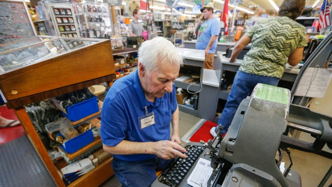 John Cope makes dog tags at Woodside's Surplus City on Tuesday, September 13, 2016. The business will be closing this fall after being open since 1946.
