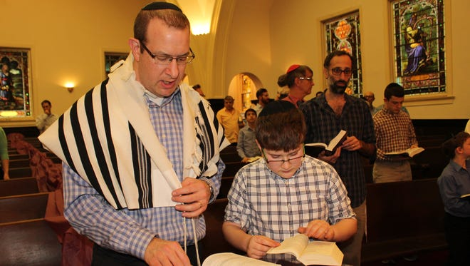 National Synagogue members Scott Reiter and his son, Ezra, pray at Temple Mishkan Israel during Sabbath services in Selma Friday night. Alvin Benn/Special to the Advertiser