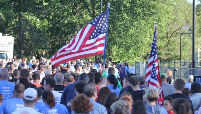 File photo of runners walking to the start of the 2016 Flag Day 5K Run and Fun Walk carrying American flags.