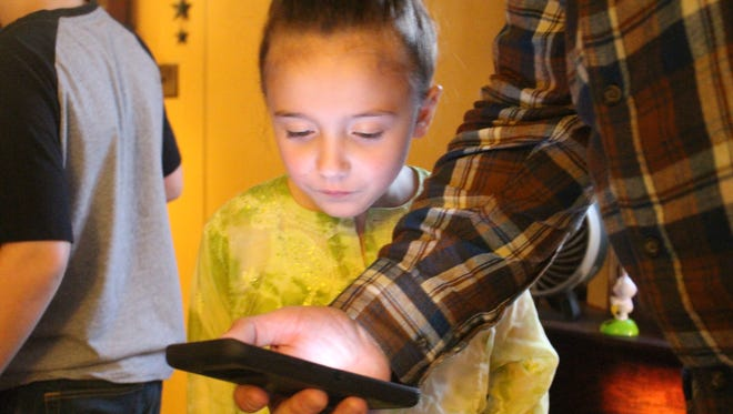 Leigha Gates, 7, looks at pictures of her dad on her uncle's phone. Her dad, Bryan Gates, died of an overdose last year. She and her two siblings write him letters and put them in a memory box at their aunt's house.