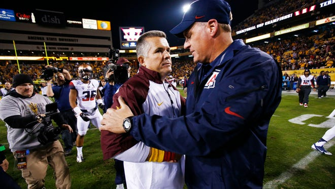 ASU coach Todd Graham shakes hands with Arizona coach Rich Rodriguez after the Sun Devils defeated the Wildcats 58-31 in the 87th Territorial Cup on Saturday, Nov. 30, 2013 in Tempe.
