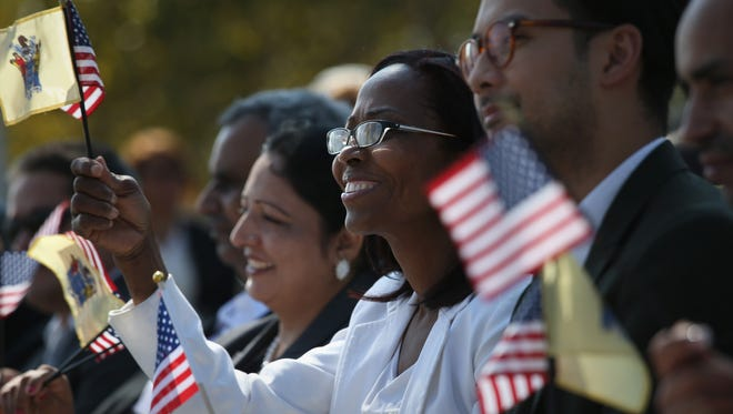 New American citizens wave flags on Constitution and Citizenship Day, September 19, this year.