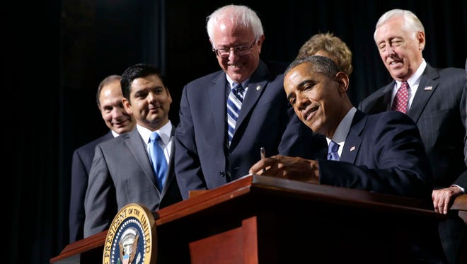 President Barack Obama, flanked by Senate Veterans Affairs Committee Chairman Sen. Bernie Sanders, I-Vt., left, and House Minority Whip Steny Hoyer of Md., right, signs H.R. 3230, the Veteransâ?? Access to Care through Choice, Accountability, and Transparency Act of 2014, Thursday, Aug. 7, 2014, at the Wallace Theater in Fort Belvoir, Va. The bill gives resources to the Department of Veterans Affairs to improve access and quality of care for veterans. (AP Photo/Jacquelyn Martin)