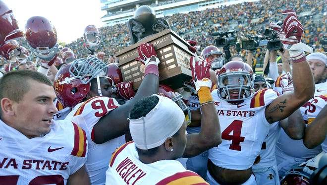 Iowa State players celebrated with the Cy- Hawk Trophy in front of their fans after their 20 - 17 win over Iowa in football game played at Kinnick Stadium in Iowa City on Saturday Sept. 13, 2014.