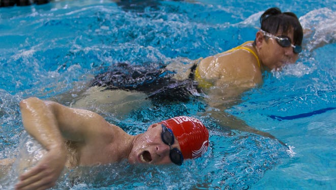Purdue University President Mitch Daniels (red cap) and Janet Winslow of West Lafayette swim March 31, 2014, at the Boilermaker Aquatic Center in West Lafayette, Ind. She's a member of iSwim Masters.