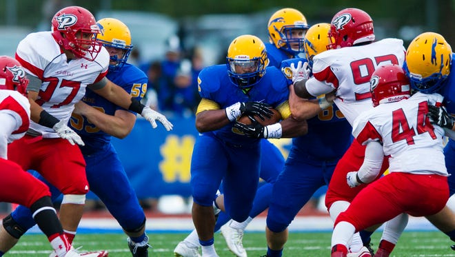 Carmel High School senior Shakir Paschall (5) rushes the ball out of the backfield during the first half of action. Carmel High School hosted Pike High School in varsity football action, Friday, September 12, 2014.