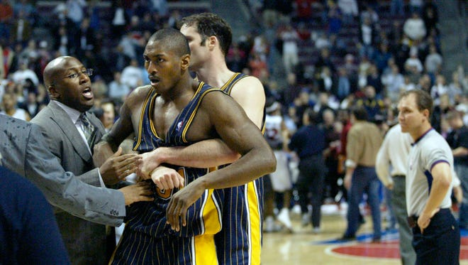 FILE - In this Nov. 19, 2004 file photo, Indiana Pacers' Ron Artest is restrained before being escorted off the court following a fight with the Detroit Pistons and fans in Auburn Hills, Mich. Artest, now known as Metta World Peace and with the New York Knicks, believes Marcus Smart can learn from the fallout that will come after the Oklahoma State All-American shoved a fan during an NCAA college basketball game at Texas Tech on Saturday, Feb. 8, 2014. Smart was suspended three games by the Big 12 on Sunday.