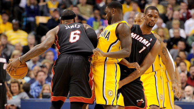 Indiana Pacers guard Lance Stephenson is called for a foul on Miami Heat forward LeBron James while pinned between James and Chris Bosh inside Bankers Life Fieldhouse, Wednesday, March 26, 2014, in Indianapolis.