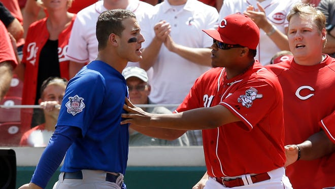 Chicago Cubs' Anthony Rizzo is held back by Cincinnati Reds' Alfredo Simon (31) at the start of a bench clearing scuffle in the 10th inning of a baseball game, Thursday, July 10, 2014, in Cincinnati.
