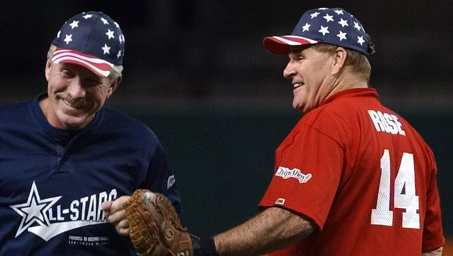 FILE - In this Sept. 22, 2002, file photo, Pete Rose, right, slaps hands with former Phildelphia Phillies Hall of Famer Mike Schmidt, left, after Schmidt hit a home run during a celebrity softball game at Cinergy Field in Cincinnati.