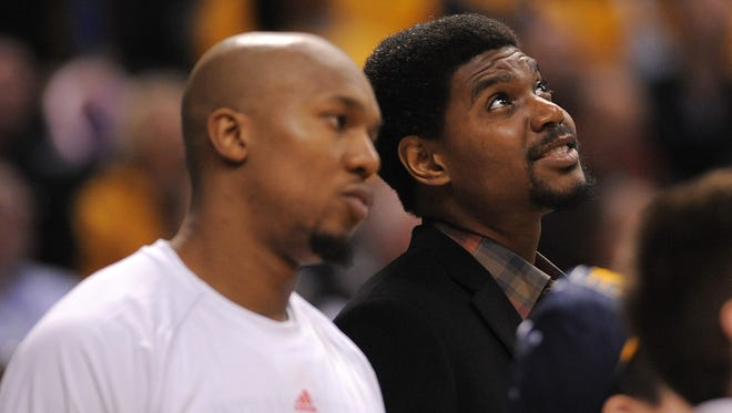 Indiana Pacers center Andrew Bynum smiles while watching the St. Elmo's Shrimp Eating Contest during a timeout against the Portland Trail Blazers inside Bankers Life Fieldhouse, February 7, 2014, in Indianapolis.