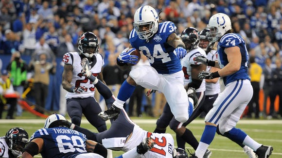 Indianapolis Colts Trent Richardson hurdles his way into the end zone for a touchdown against the Houston Texans during the first half, Sunday, December 15, 2013, at Lucas Oil Stadium.