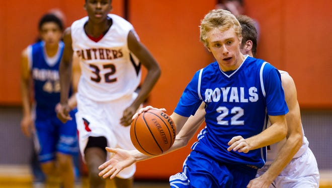 Hamilton Southeastern High School senior Brendan Burns (22) is fouled by North Central High School senior Michael Loggan (24) as he brings the ball up court during the second half of high school varsity basketball action Saturday, Dec. 21, 2013, at North Central High School. Hamilton Southeastern defeated North Central 79-74.