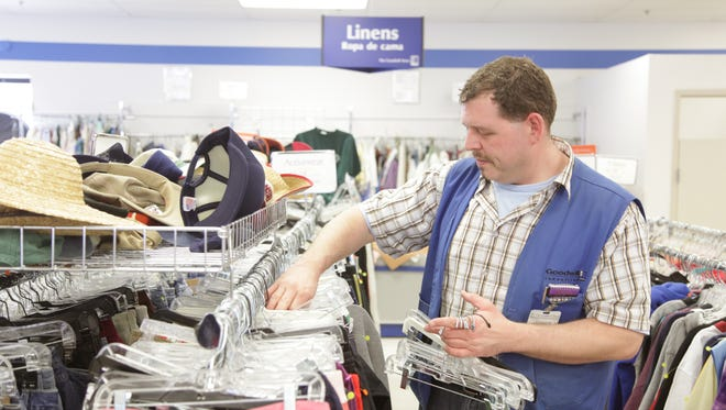 (File Photo)  Store manager Joseph Samuel collects empty hangars from a rack of clothing at the Goodwill store in Iowa City, on Monday, Jan. 12, 2009.