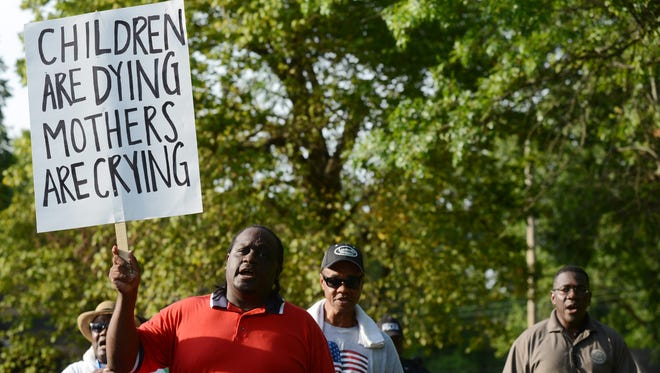 Darrel Brown (center) walks during an anti-crime march on Friday starting on Hollywood Drive. Supporters shouted, 'Up with hope! Down with dope!' as they walked around downtown Jackson neighborhoods.